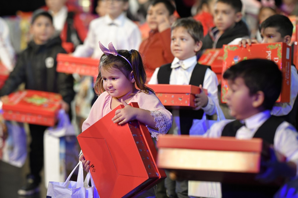 Children hold presents received after a Christmas show for children in care, in Bucharest, Romania, Wednesday, Dec. 18, 2019. Romania has more than 50...