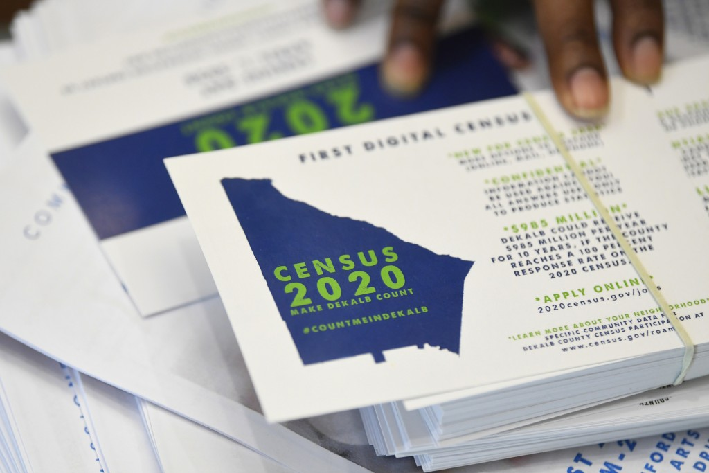 FILE - In this Aug. 13, 2019, file photo a worker gets ready to pass out instructions in how fill out the 2020 census during a town hall meeting in Li...