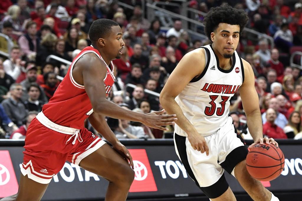 Louisville forward Jordan Nwora (33) tries to get around Miami (Ohio) guard Myja White (11) during the second half of an NCAA college basketball game ...