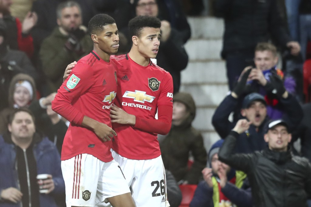 Manchester United's Marcus Rashford, left, celebrates with Manchester United's Mason Greenwood after scoring his side's first goal, during the English...