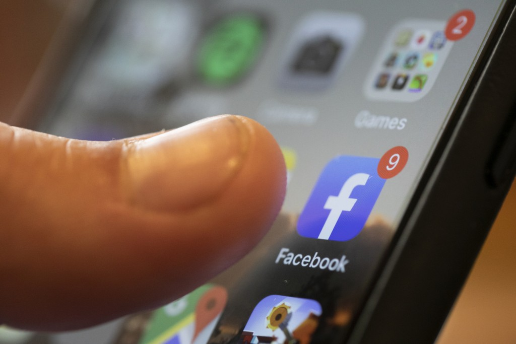 FILE - In this Aug. 11, 2019, file photo an iPhone displays the Facebook app in New Orleans. Facebook says it won't allow interference with the U.S. c...