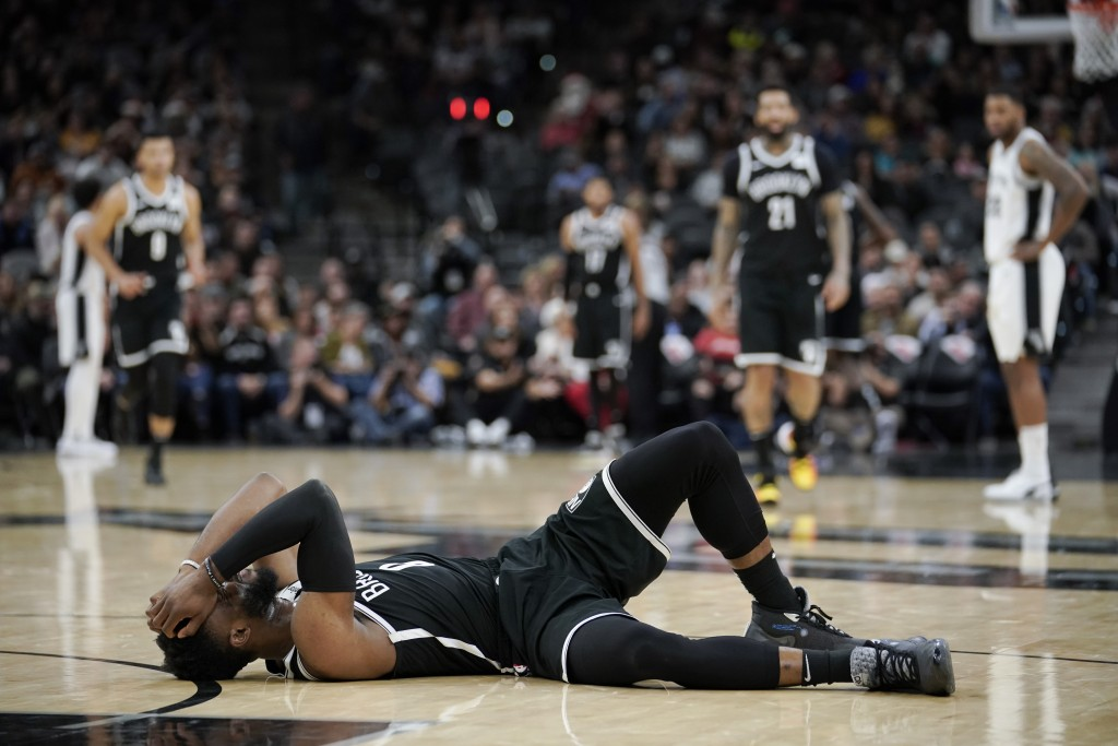 Brooklyn Nets' David Nwaba lies injured on the court during the second half of the team's NBA basketball game against the San Antonio Spurs, Thursday,...