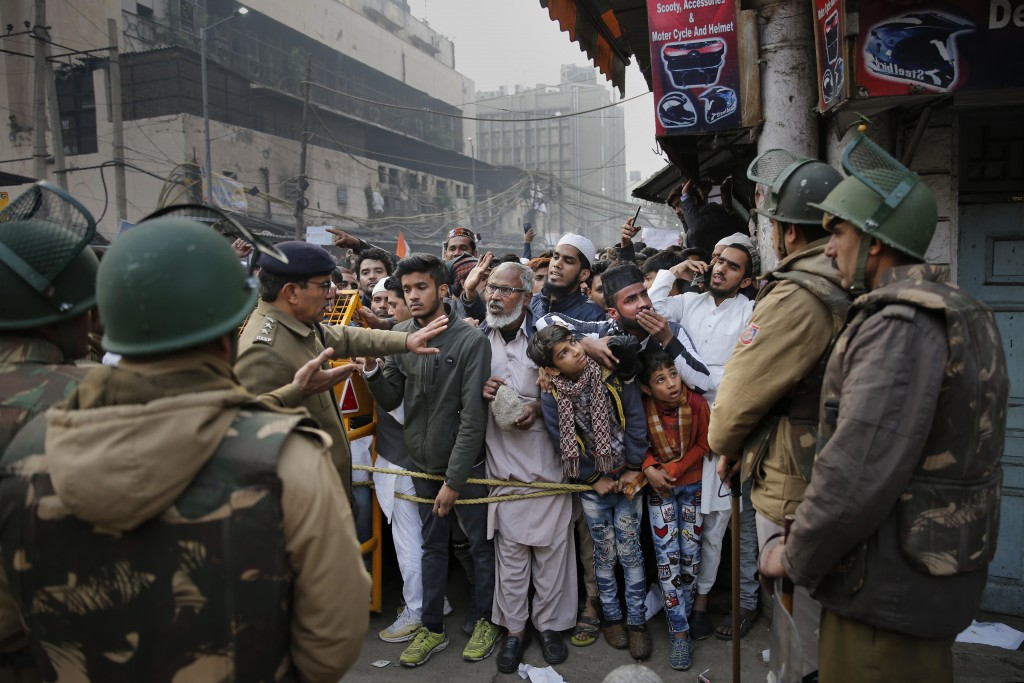 Indian policemen stop protesters at a police barricade in New Delhi, India, Friday, Dec. 20, 2019. Police banned public gatherings in parts of the Ind...