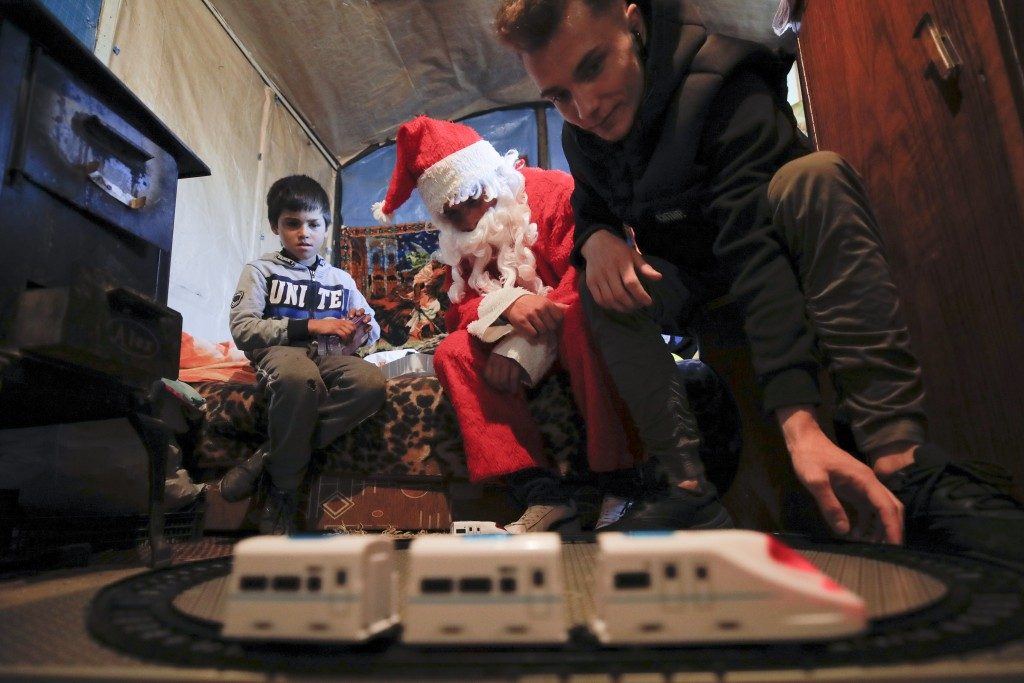 In this photo taken on Sunday, Dec. 15, 2019, Andrei, 19 years old, who lives transit home ran by Florin Catanescu, looks at a toy train brought as a ...