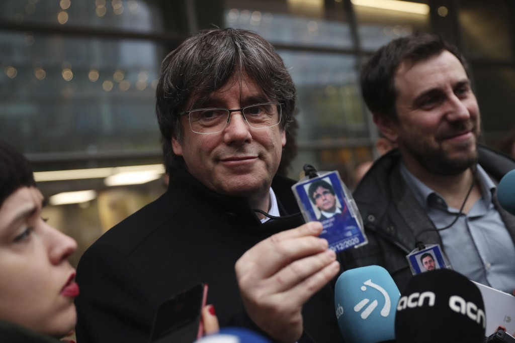 Catalonia's former regional president Carles Puigdemont, center, shows his accreditation badge as he stands next to former Catalan regional minister A...