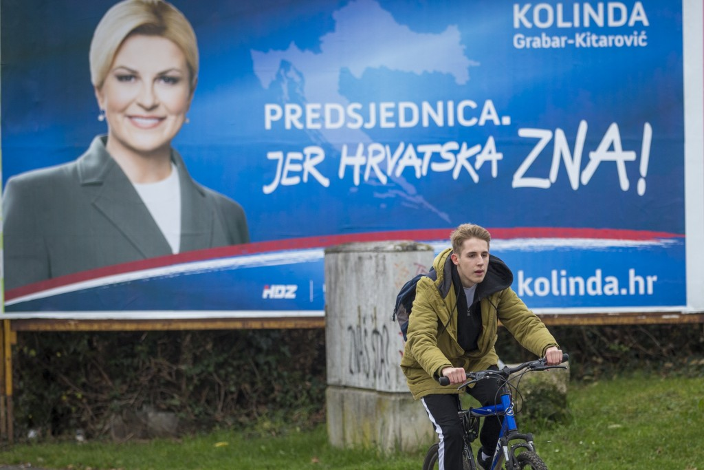 In this Thursday, Dec.19, 2019 photo, a cyclist rides past a poster of presidential candidate Kolinda Grabar Kitarovic in Zagreb, Croatia. The Europea...