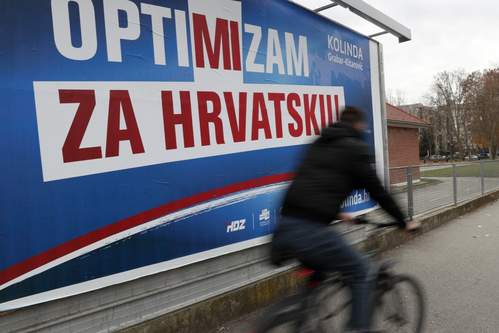 In this Thursday, Dec. 19, 2019 photo, a cyclist rides past a poster of presidential candidate Kolinda Grabar Kitarovic in Zagreb, Croatia. The Europe...