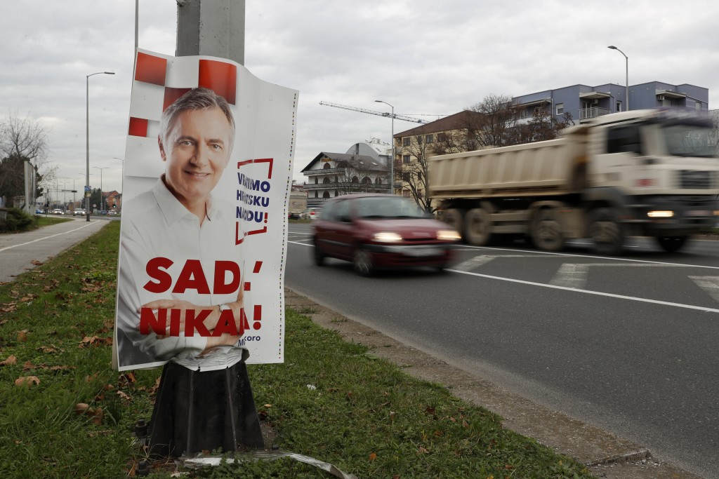 In this Thursday, Dec. 19, 2019 photo, traffic passes a poster of presidential candidate Miroslav Skoro in Zagreb, Croatia. The European Union's newes...