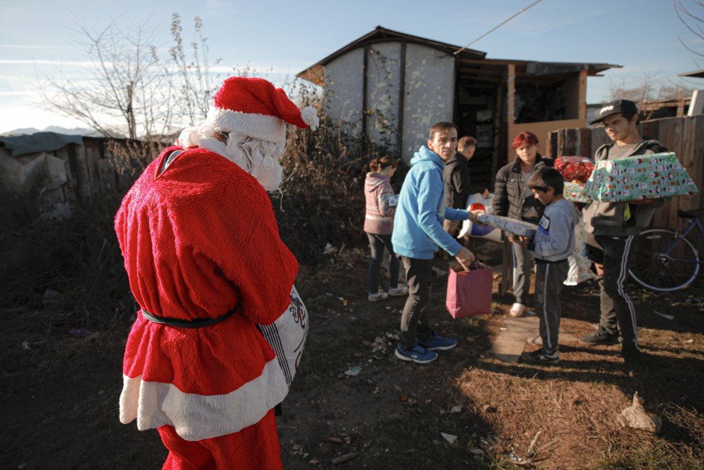 In this photo taken on Sunday, Dec. 15, 2019, Florin Catanescu, 41, center right, caries presents for a poor family, along with a youngster he looks a...