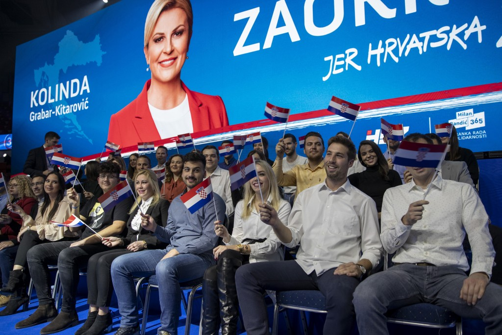 In this Thursday, Dec. 19, 2019 photo, supporters wave flags under a photo of presidential candidate Kolinda Grabar Kitarovic at a rally in Zagreb, Cr...