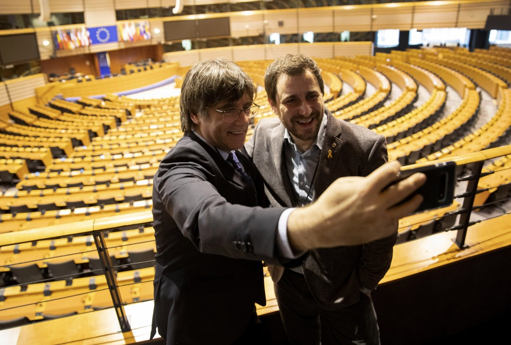 Catalonia's former regional president Carles Puigdemont, left, and former Catalan regional minister Antoni Comin take a selfie overlooking the plenary...