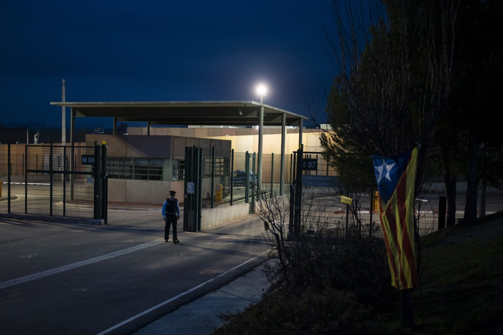 An estelada or independence flag, hangs from a tree as a policeman walks past the entrance of Lledoners prison, where former Catalan vice president Or...