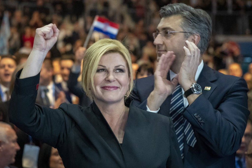 In this Thursday, Dec. 19, 2019 photo, presidential candidate Kolinda Grabar Kitarovic, left, and prime minister Andrej Plenkovic greet supporters at ...