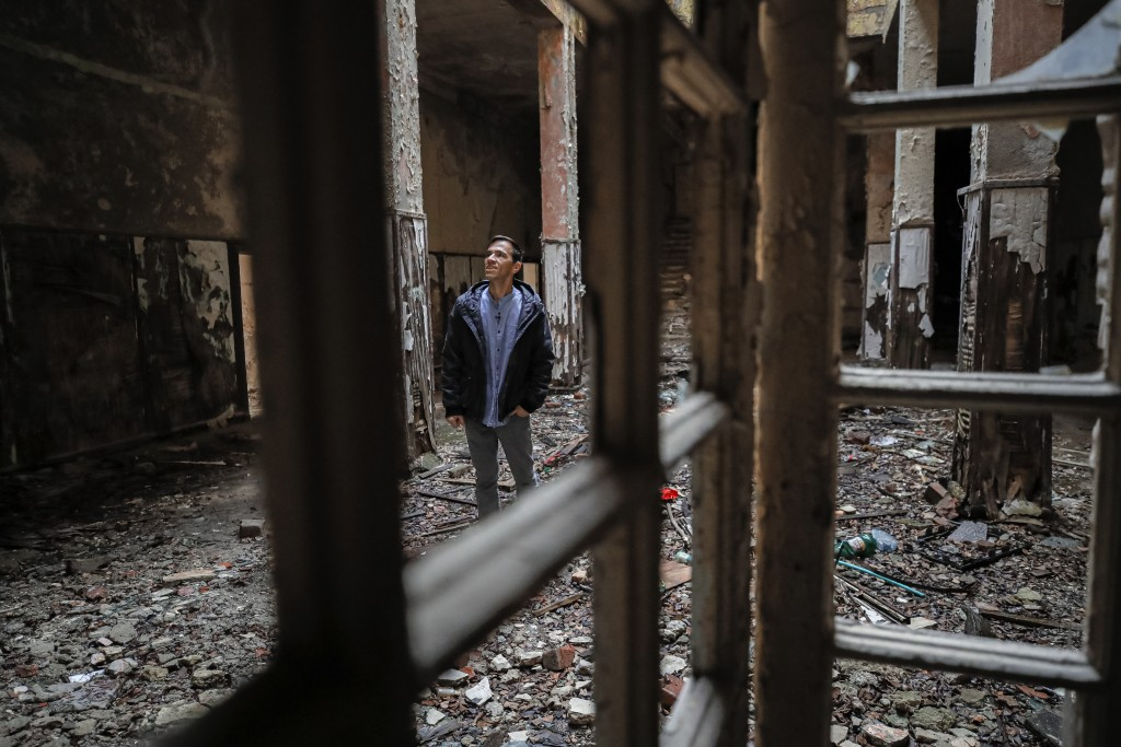 In this photo taken on Monday, Dec. 16, 2019, Florin Catanescu, 41, walks through the ruins of the state orphanage that was his home between 1988 and ...