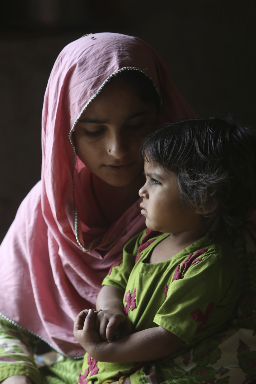 FILE - In this May 16, 2019 file photo, Pakistani mother Parveen sits with her three-year-old Ume Kulssom both infected with HIV, sit in their home in...