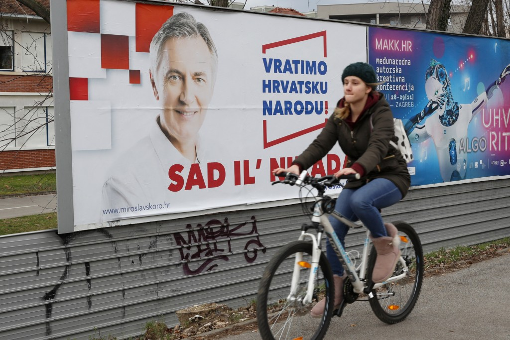 In this Thursday, Dec. 19, 2019 photo, a cyclist rides past a poster of presidential candidate Miroslav Skoro in Zagreb, Croatia. The European Union's...
