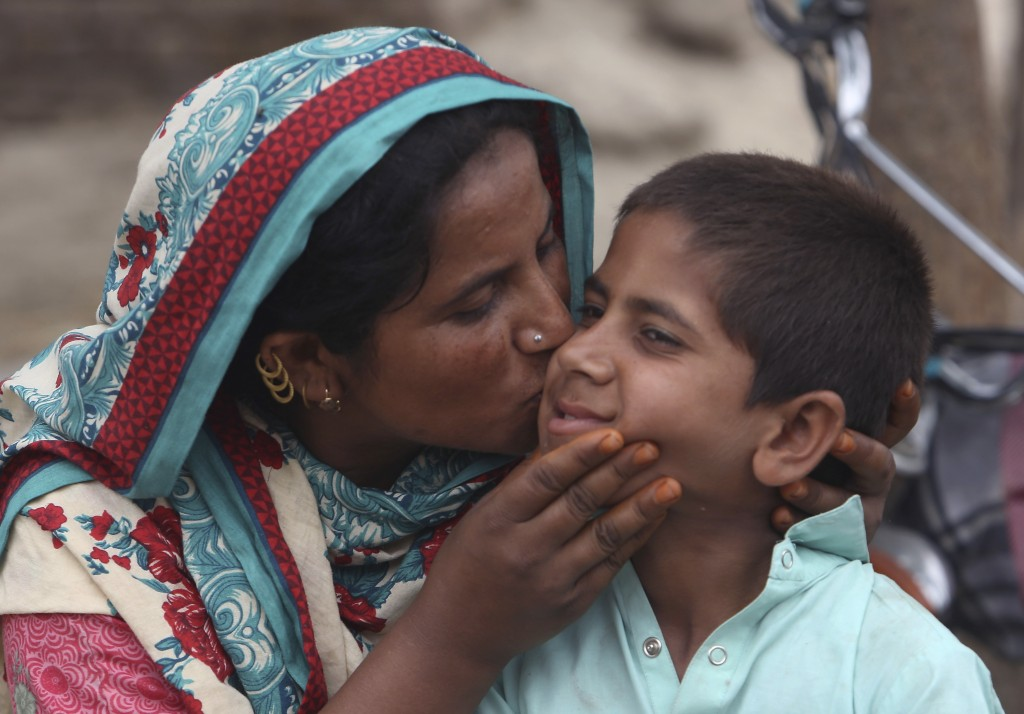 FILE - In this May 16, 2019 file photo, A Pakistani mother kisses her son Ali Raza, 10, reportedly infected with HIV in a village near Ratodero, in so...