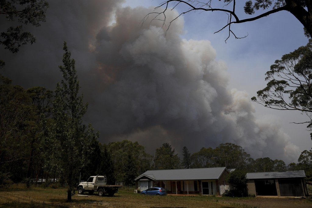 A home stands as smoke from the Grose Valley fire rises in the distance in Bilpin, west of Sydney, Saturday, Dec. 21, 2019. Australia's most populous ...
