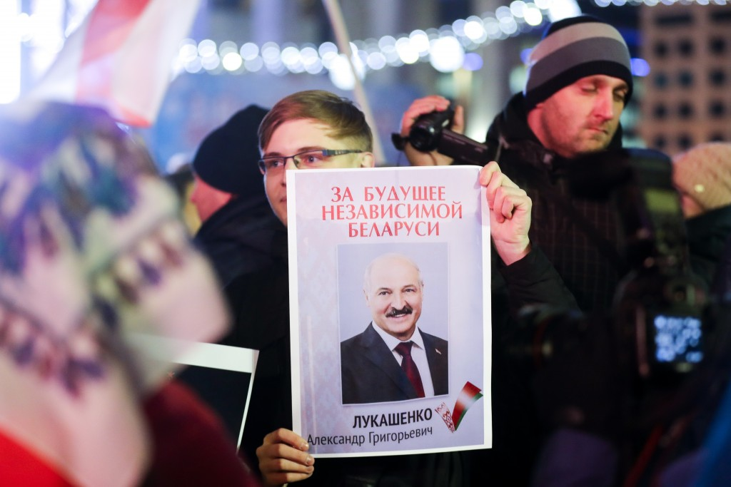 """A demonstrator holds a poster with a portrait of Belarusian President Alexander Lukashenko and words reading """"for the future of independent Belarus"""" d..."""