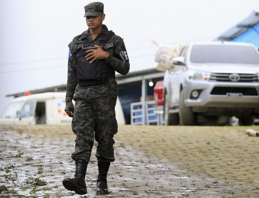 A military police officer walks past a pick-up truck loaded with the bodies of dead inmates that is parked in the Tela prison where at least 18 prison...
