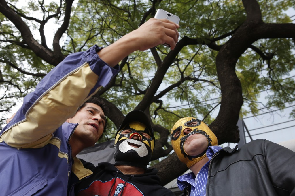 "Fans take a selfie with Mexican wrestlers Super Muñeco, center, and Sanguinario, right, before ""lucha libre"" match in Mexico City, Saturday, Dec. 21, ..."