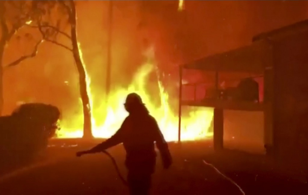 In this image made from video taken and provided by NSW Rural Fire Service via their twitter account, a firefighter sprays water on a fire moving clos...