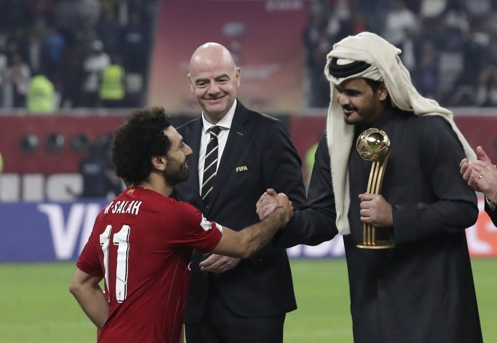 FIFA president Gianni Infantino, center, watches as Sheikh Joaan bin Hamad bin Khalifa Al Thani, right, shake hands with Liverpool's Mohamed Salah, le...