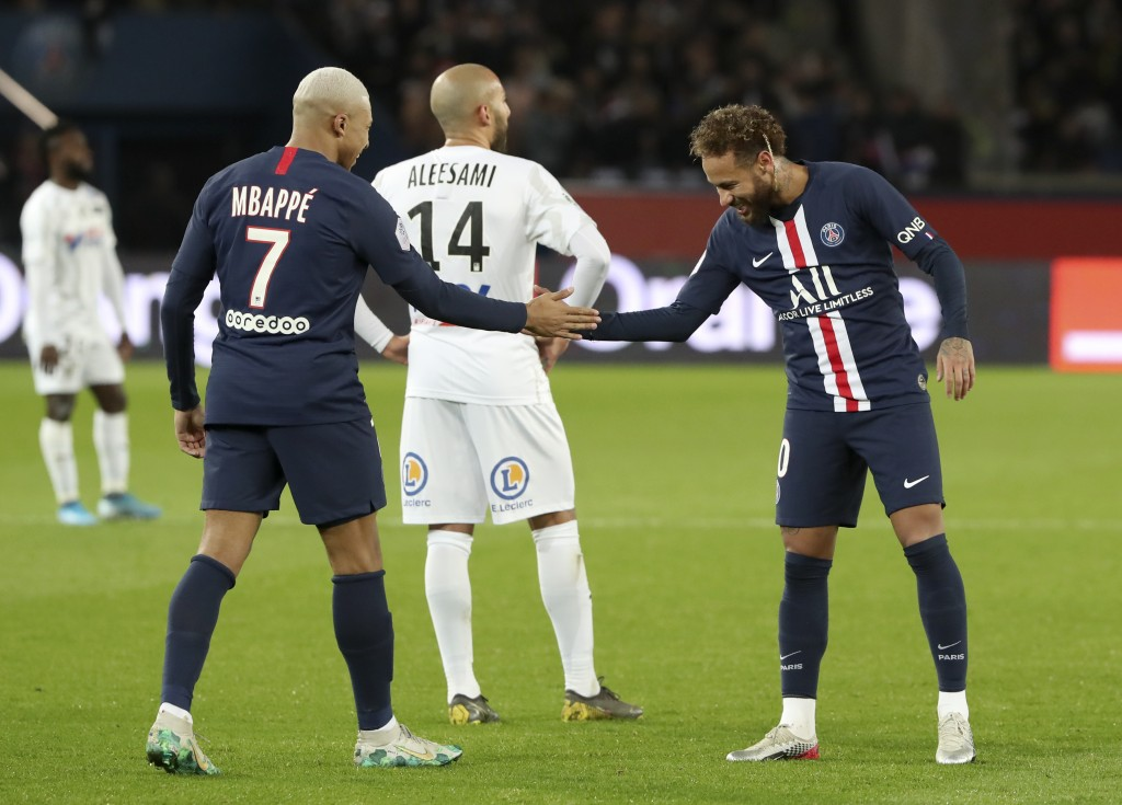 PSG's Kylian Mbappe, left, and Neymar celebrate after scoring their side's third goal during the League One soccer match between Paris Saint Germain a...