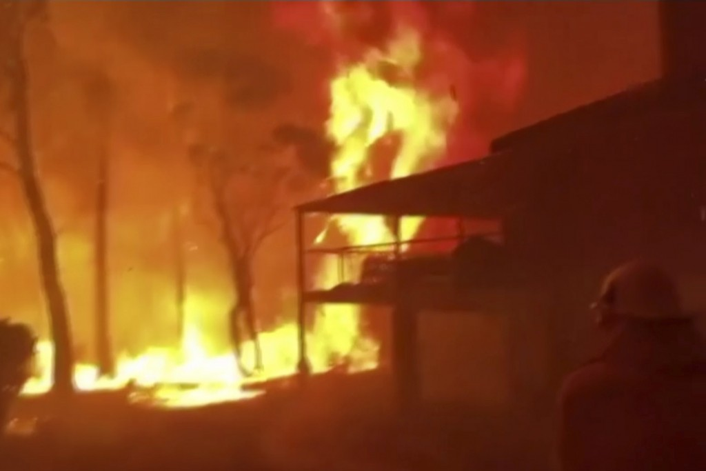 In this image made from video taken and provided by NSW RFS via their twitter account, a firefighter sprays water on a fire moving closer to a home in...