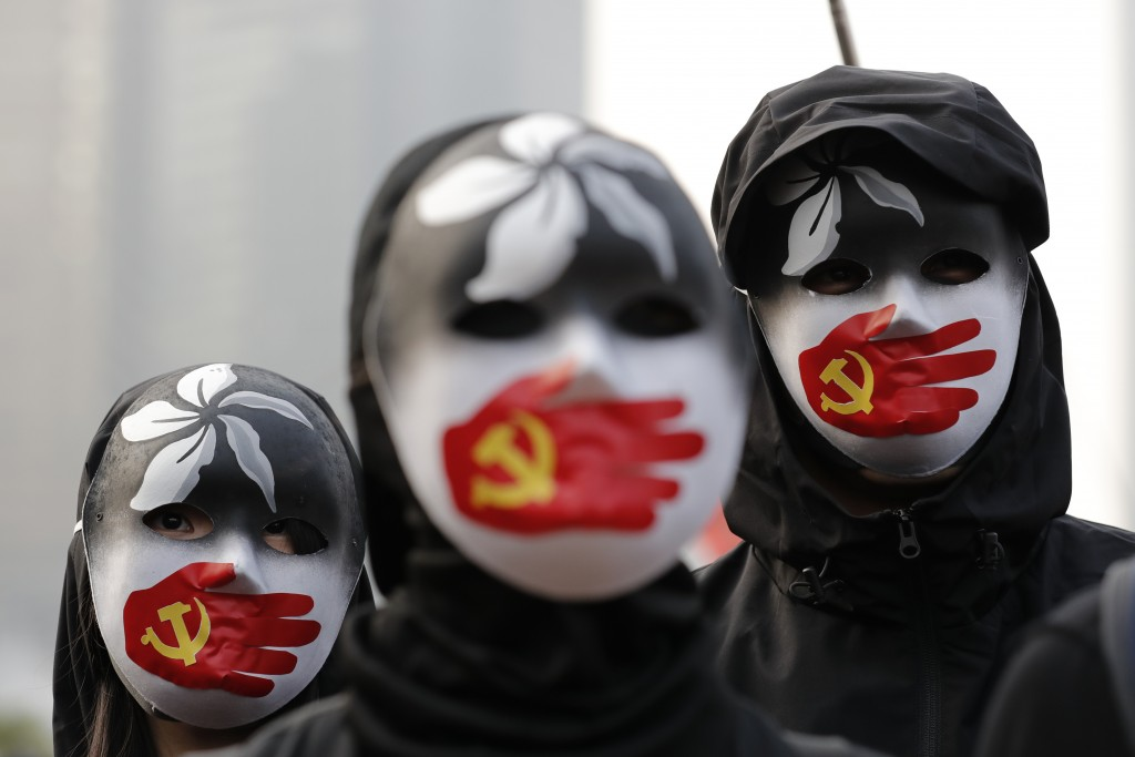 In this Sunday, Dec. 22, 2019, file photo, people wearing masks stand during a rally to show support for Uighurs and their fight for human rights in H...