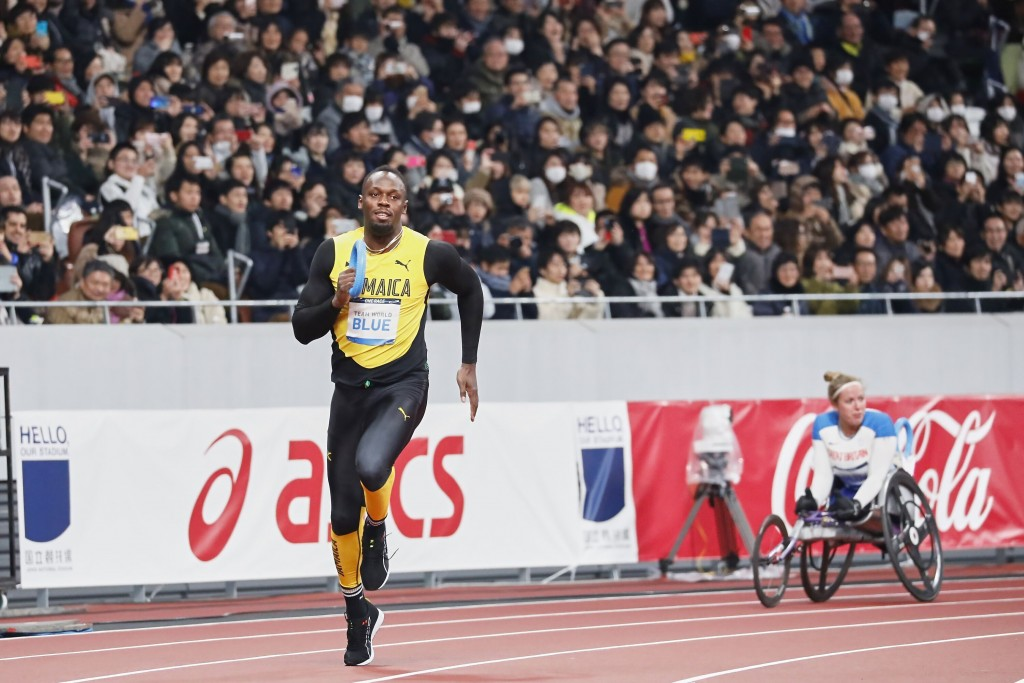 In this photo provided by Japan Sports Council (JSC), Olympics gold medalist Usain Bolt, left, of Jamaica runs at the opening ceremony of the New Nati...