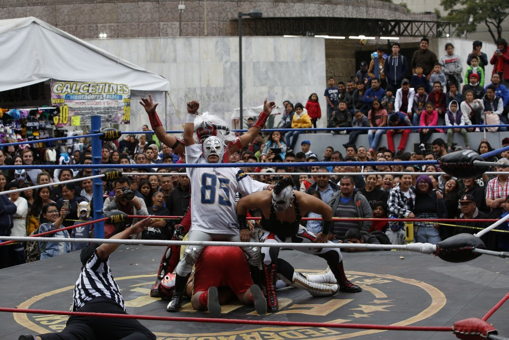 "Mexican wrestlers fight during a public bout in Mexico City, Saturday, Dec. 21, 2019. Mexican wrestling, otherwise known as the ""lucha libre,""  is a h..."