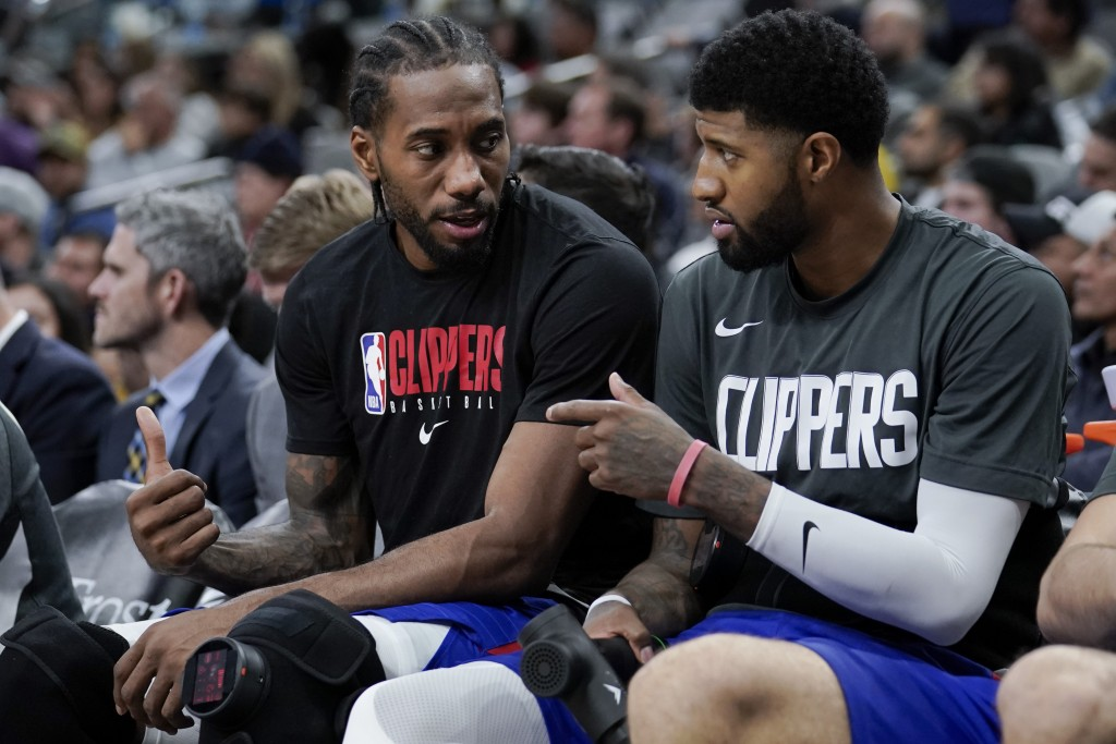 Los Angeles Clippers' Kawhi Leonard, left, and Paul George talk on the bench during the second half of an NBA basketball game against the San Antonio ...