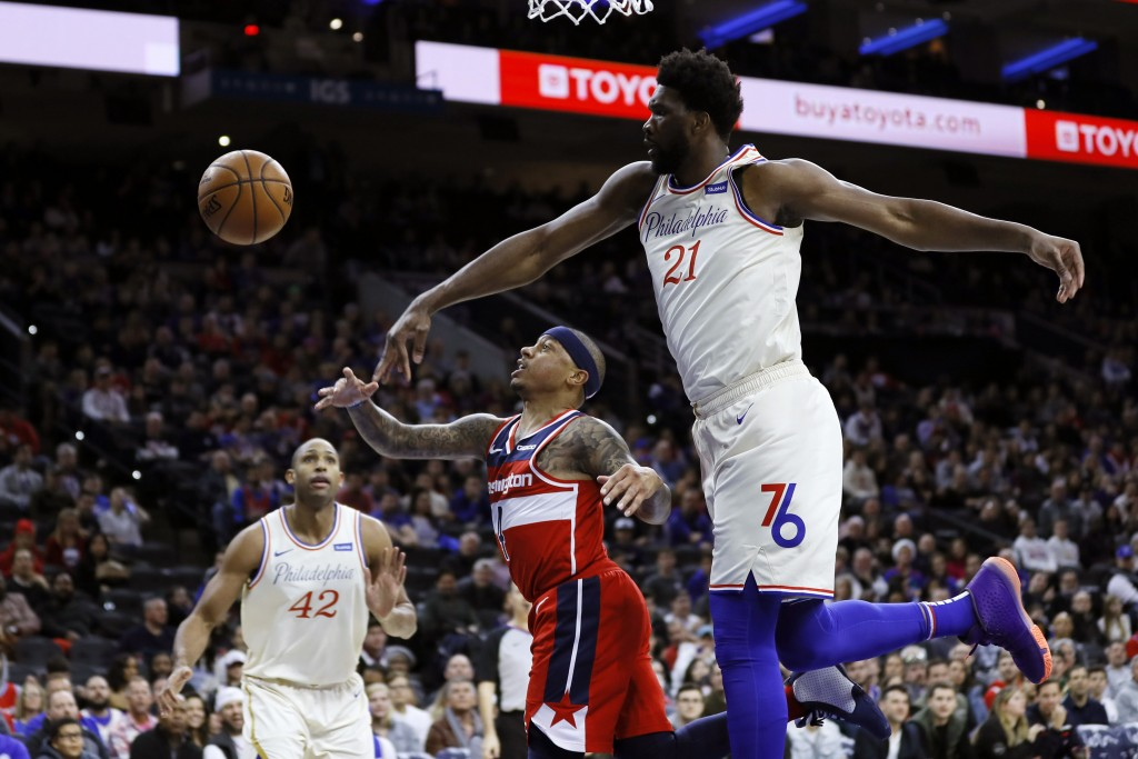Philadelphia 76ers' Joel Embiid, right, blocks a shot by Washington Wizards' Isaiah Thomas, center, during the first half of an NBA basketball game, S...