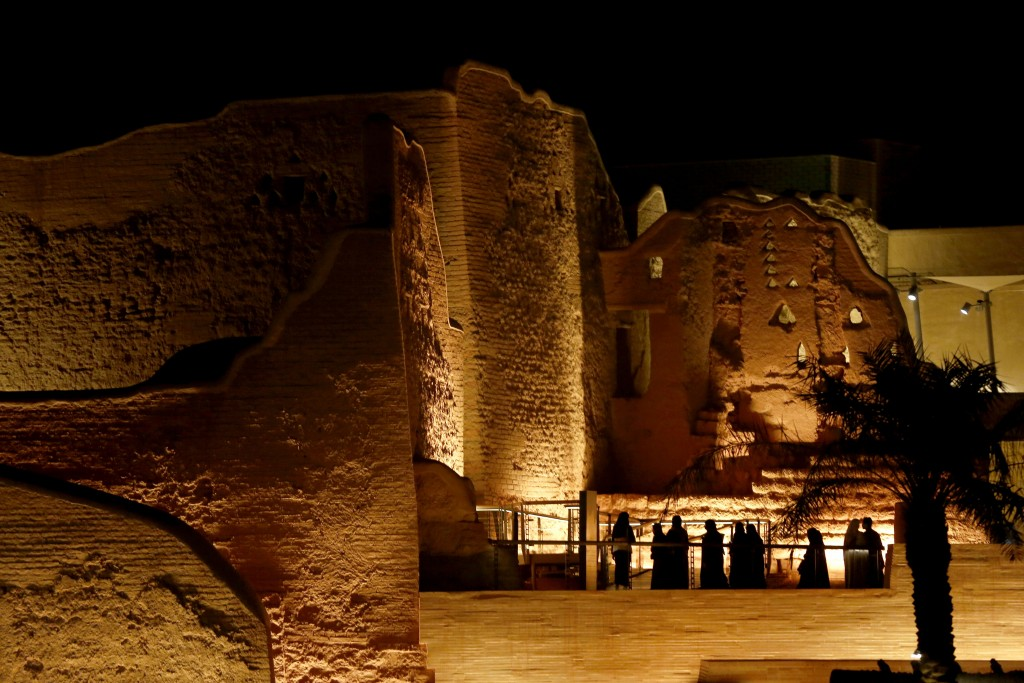 In this Dec. 13, 2019 photo, light illuminates the walls of the historical Diriyah site as visitors line up to enter the Diriyah Oasis amusement park ...