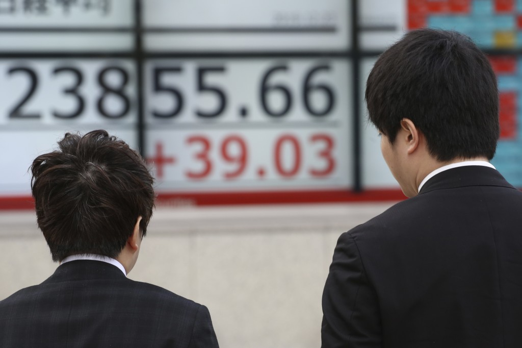 People walk by an electronic stock board of a securities firm in Tokyo, Monday, Dec. 23, 2019. Shares were mixed Monday in quiet trading ahead of Chri...