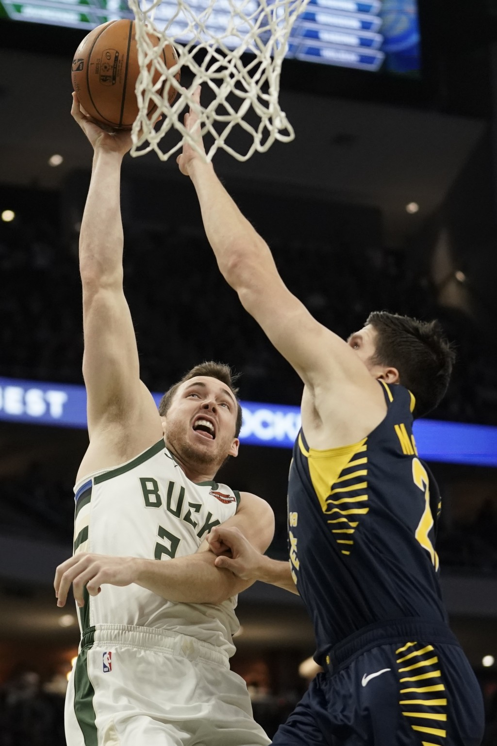 Milwaukee Bucks' Pat Connaughton is fouled by Indiana Pacers' Doug McDermott as he shoots during the first half of an NBA basketball game Sunday, Dec....