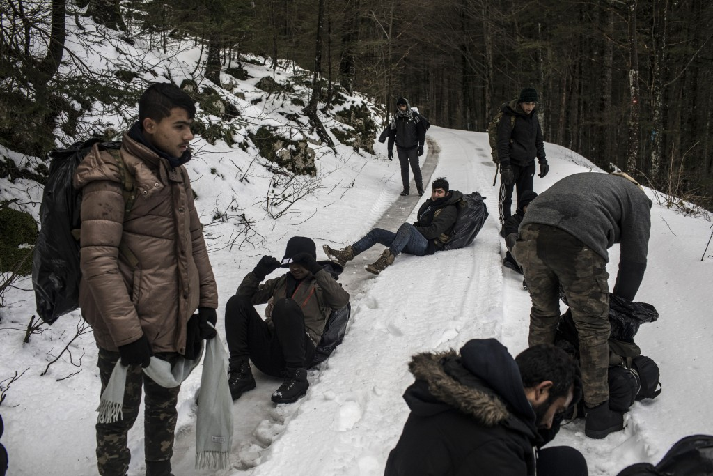 In this picture taken Sunday Dec. 15, 2019, a group of Afghan migrants take a break as they walk through the mountains in an area believed to be litte...