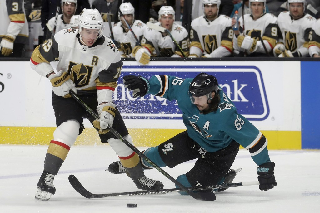 Vegas Golden Knights right wing Reilly Smith (19) reaches for the puck over San Jose Sharks defenseman Erik Karlsson (65) during the second period of ...