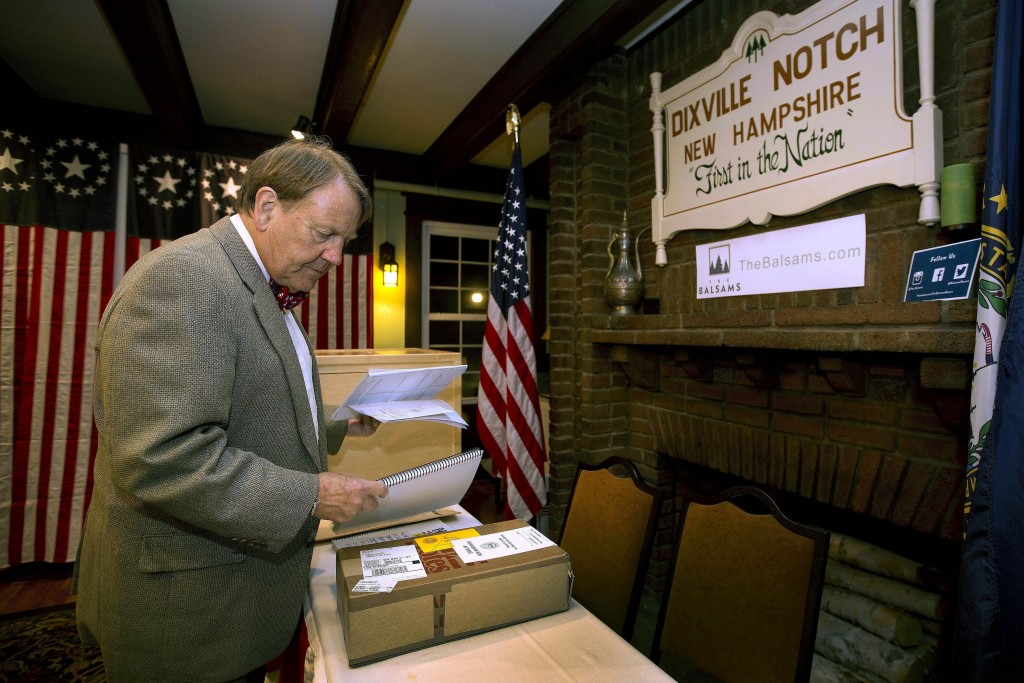 FILE - In this Nov. 7, 2016, file photo, Town moderator Tom Tillotson arrives with ballots as voters get ready to cast their votes just after midnight...