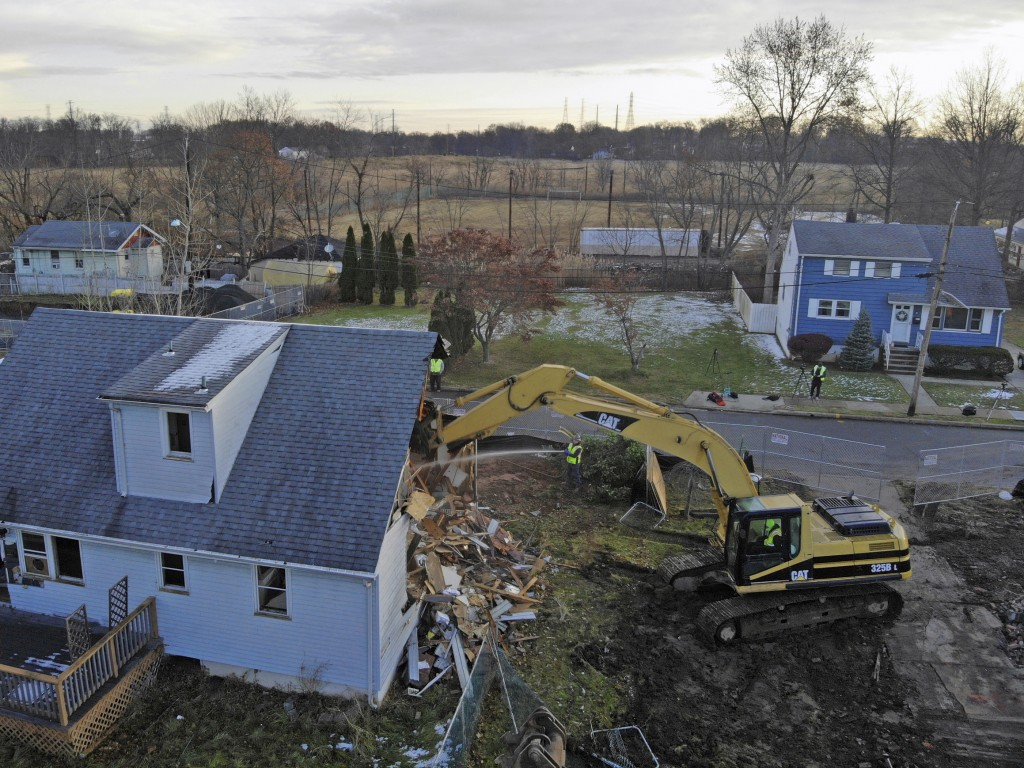 A demolition crew takes down a house in Woodbridge, N.J., on Thursday, Dec. 5, 2019. The homeowner took a buyout through a program that purchases hous...