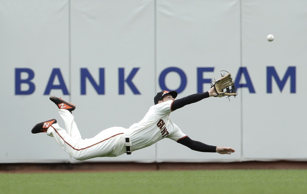 FILE  - In this June 15, 2019, file photo, San Francisco Giants left fielder Mike Yastrzemski dives to catch a fly ball hit by Milwaukee Brewers' Yasm...