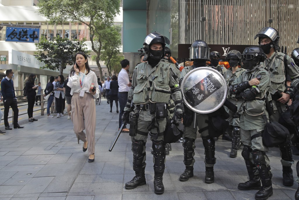 In this Monday, Nov. 11, 2019, photo, riot police stand guard in the Central district of Hong Kong. Sellers of luxury goods that are easily peddled by...