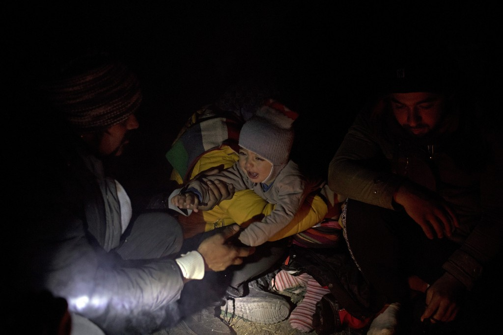 In this picture taken Thursday Dec. 12, 2019, Omar, 1, a Syrian refugee from Aleppo, cries while his mother Fatma, 24, tries to change his diaper befo...