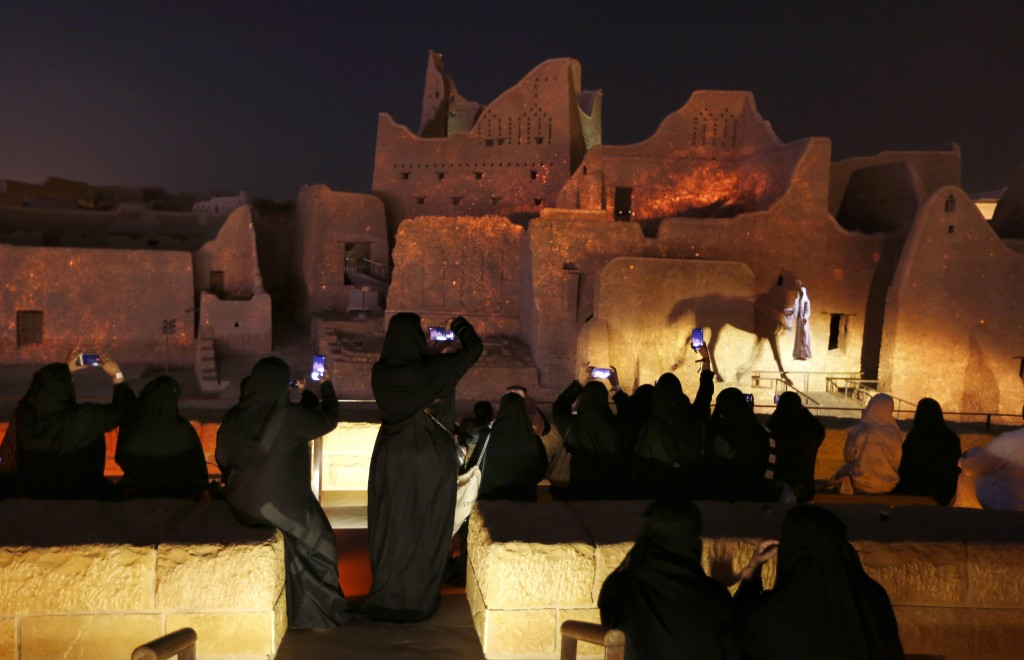 In this Dec. 13, 2019 photo, visitors film the historical Diriyah site at the Diriyah Oasis amusement park in Diriyah on the outskirts of Riyadh, Saud...