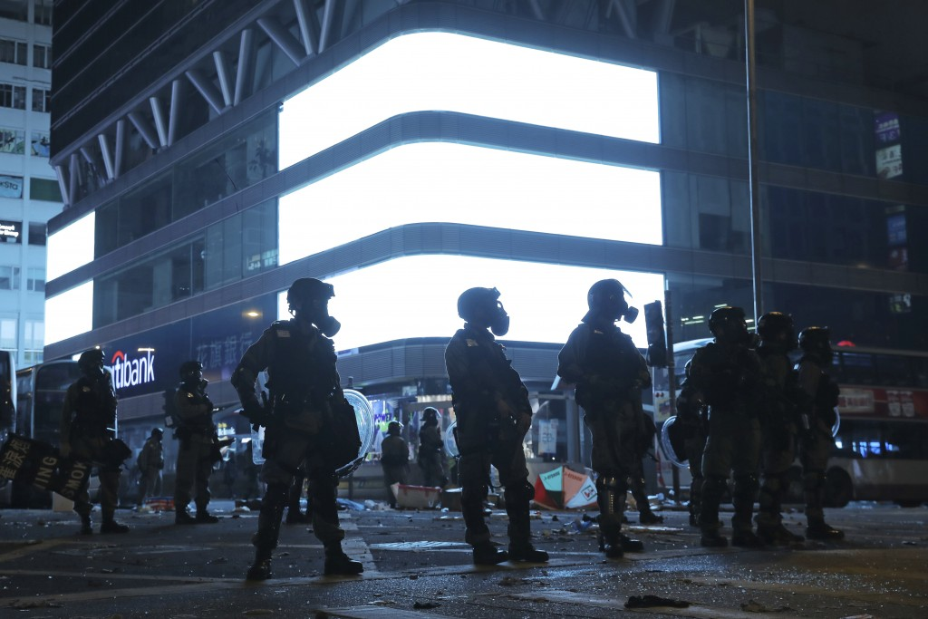 In this Monday, Nov. 11, 2019 photo, riot police stand guard in Mongkok, a shopping district of Hong Kong. Sellers of luxury goods that are easily ped...