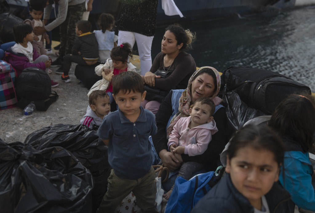 FILE - In this Tuesday, Oct. 22, 2019 file photo refugees and migrants wait for buses after their arrival to the port of Elefsina, near Athens, Greece...