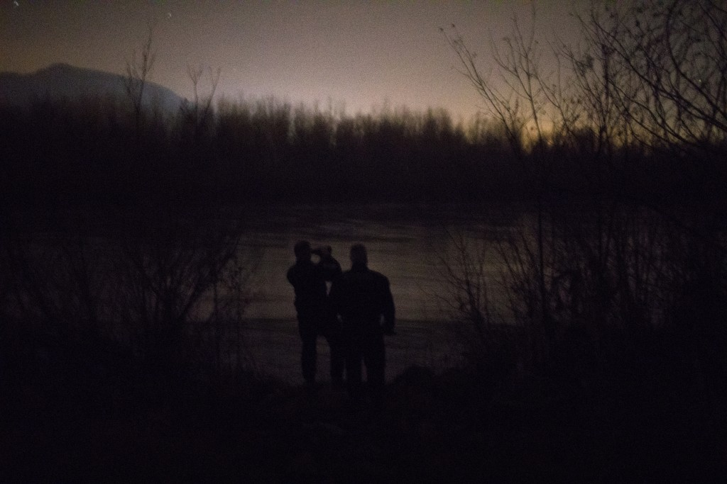 In this picture taken Monday Dec. 16, 2019, Bosnian police inspect the shore of the river Drina bordering between Bosnia and Serbia in search of migra...