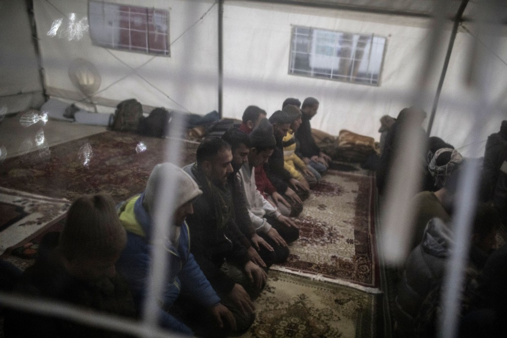 In this picture taken Thursday Dec. 12, 2019 a group of migrants, mostly form Pakistan and Afghanistan pray at a makeshift mosque at temporary recepti...