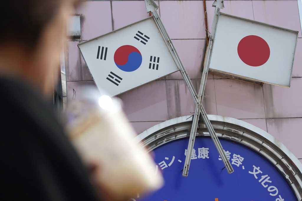 FILE - In this Aug. 2, 2019, file photo, a woman walks past an advertisement featuring Japanese and South Korean flags at a shop in Shin Okubo area in...